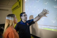 A crop sciences instructor  discusses a projected weather map with an undergraduate female student.