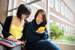 Students look at a phone in the Student Dining and Residential Programs Building.